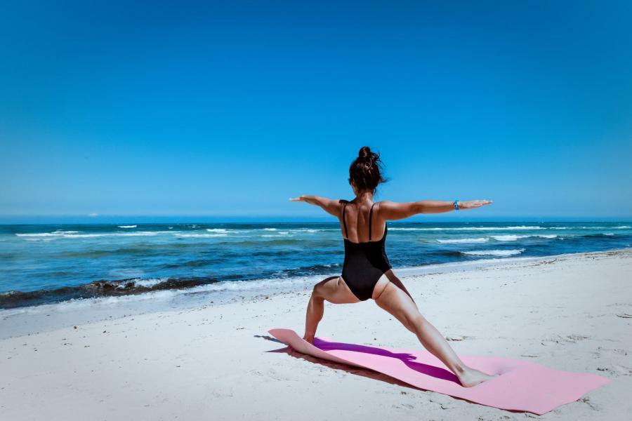 Chica en bañador practicando yoga en la playa