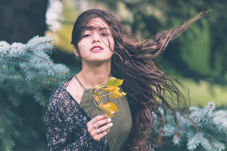 Chica morena en el bosque sujetando una hoja amarilla