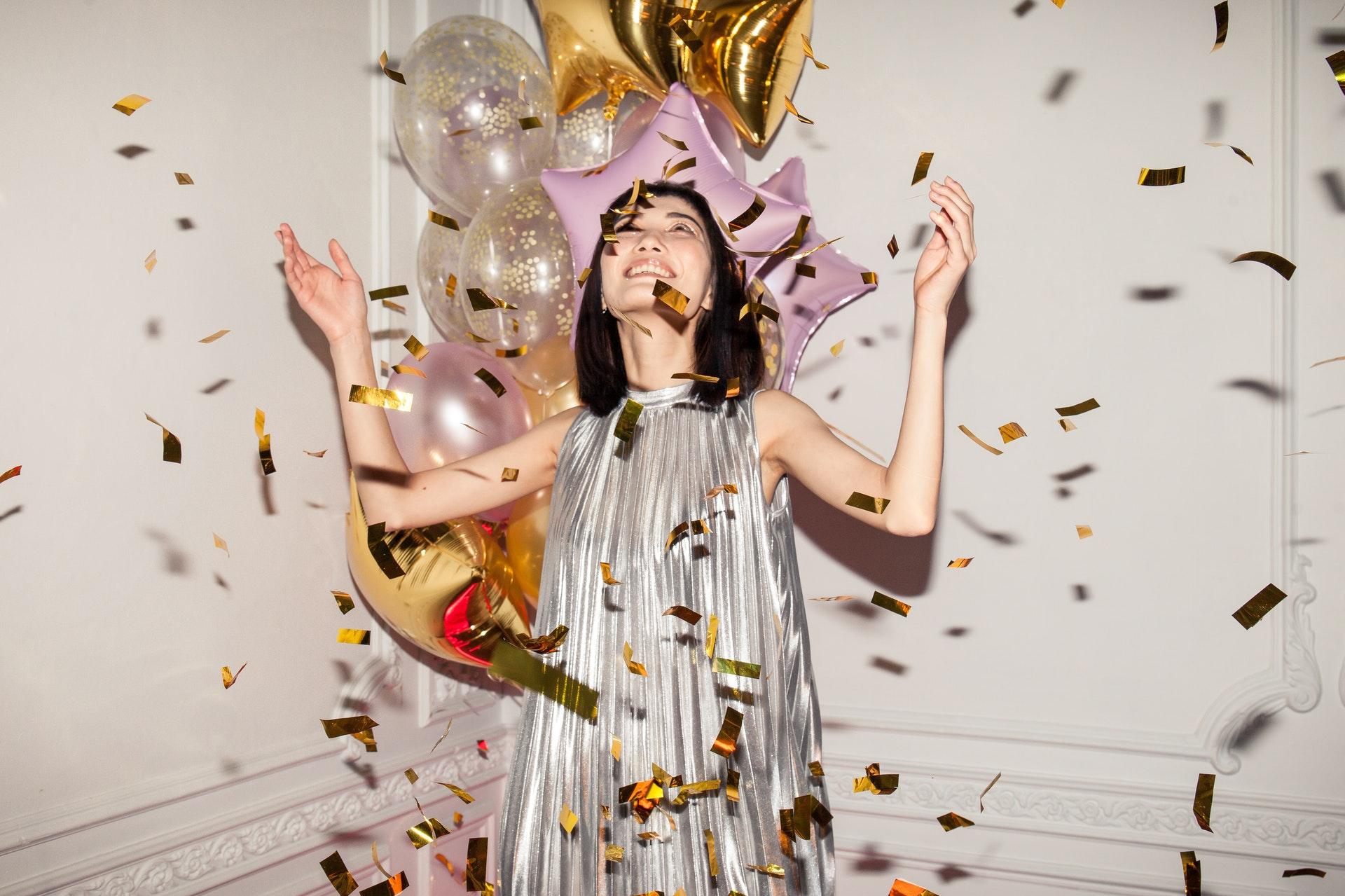 Chica sonriendo con confetis y globos hinchables