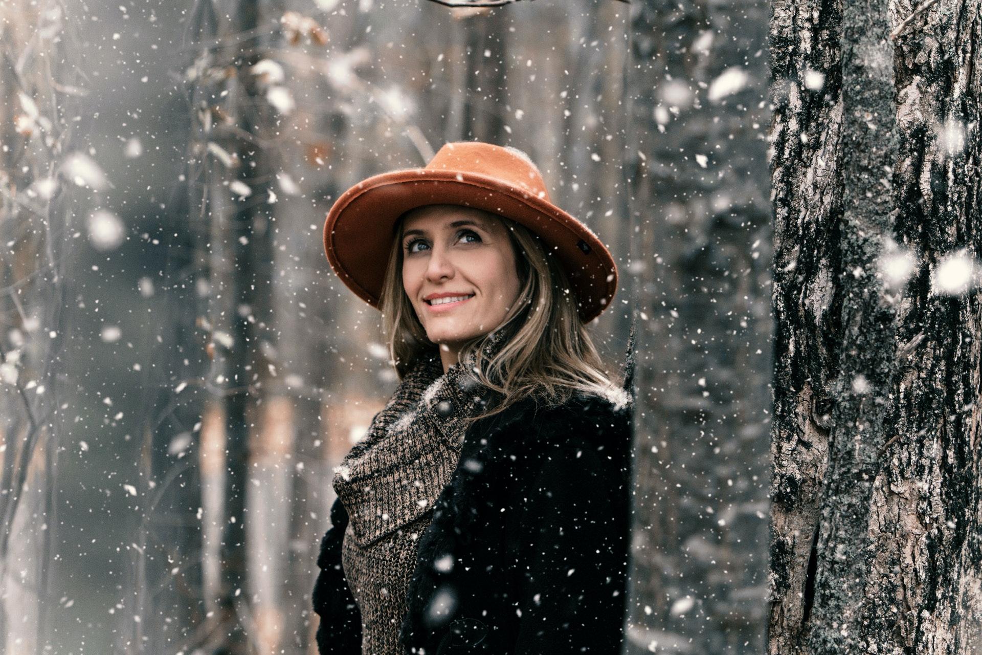 Mujer con gorro naranza en un bosque mientras nieva