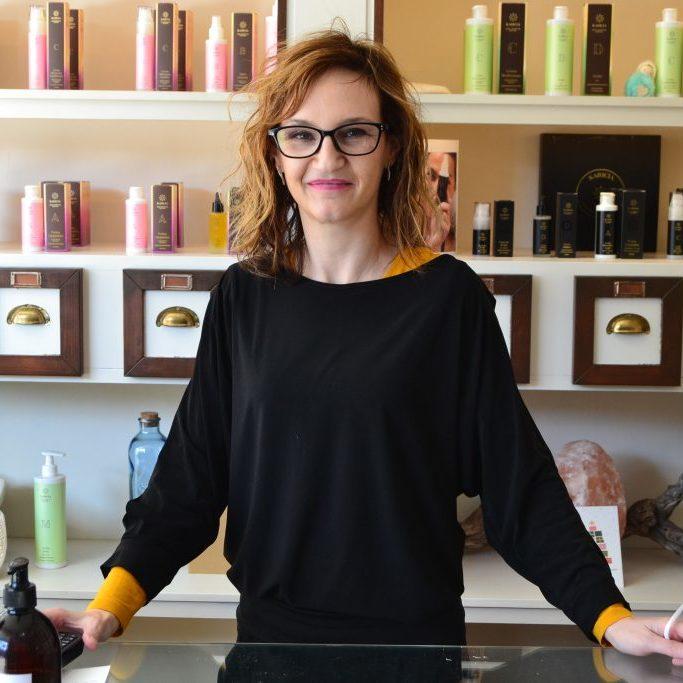 Mujer centro estetica enfrente del mostrador con productos karicia