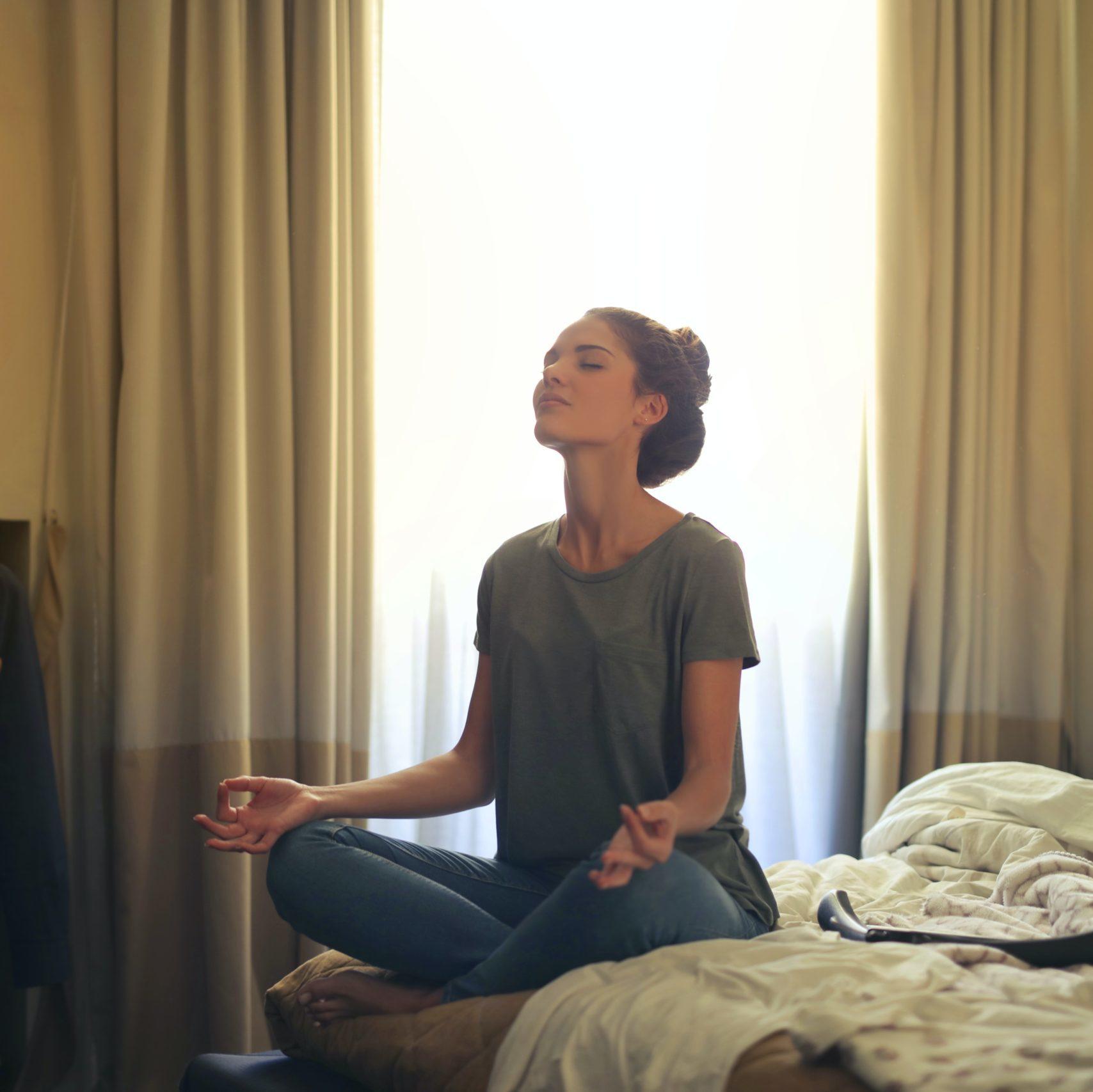 Chica sentada en la cama de su cuarto meditando