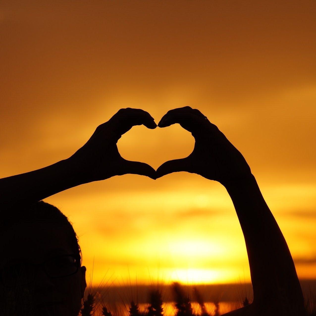 Manos crando la forma de un corazón enfrente de un atardecer