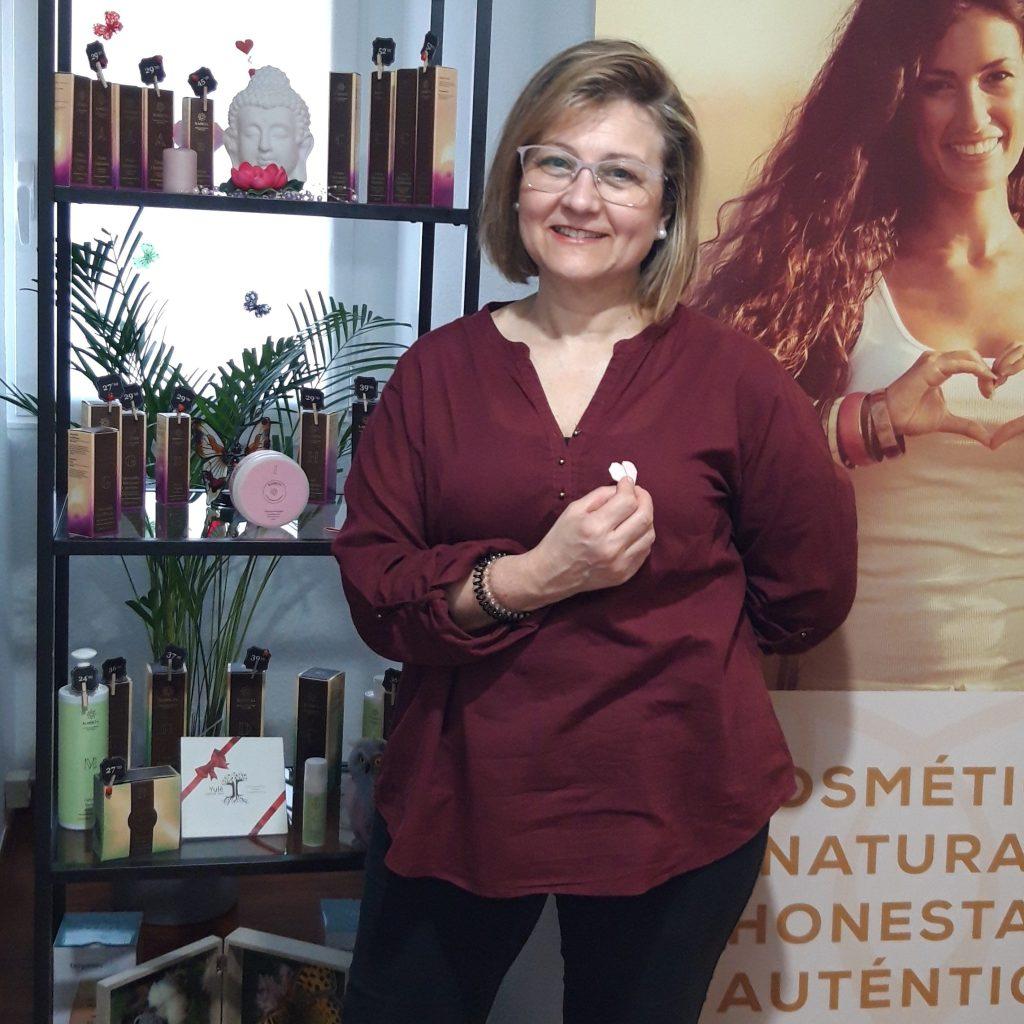 Mujer de centro estetico sonriendo en frente de productos karicia