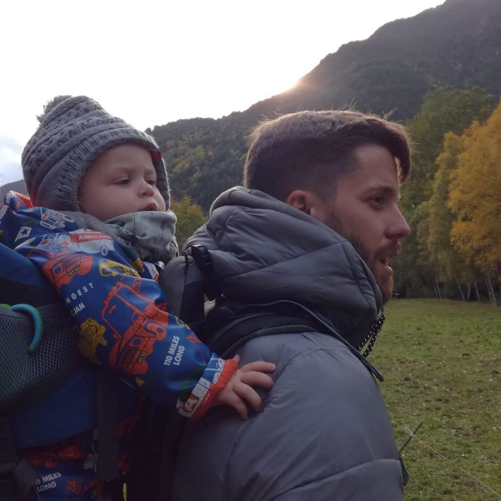 Chico con su hijo pequeño paseando por la montaña