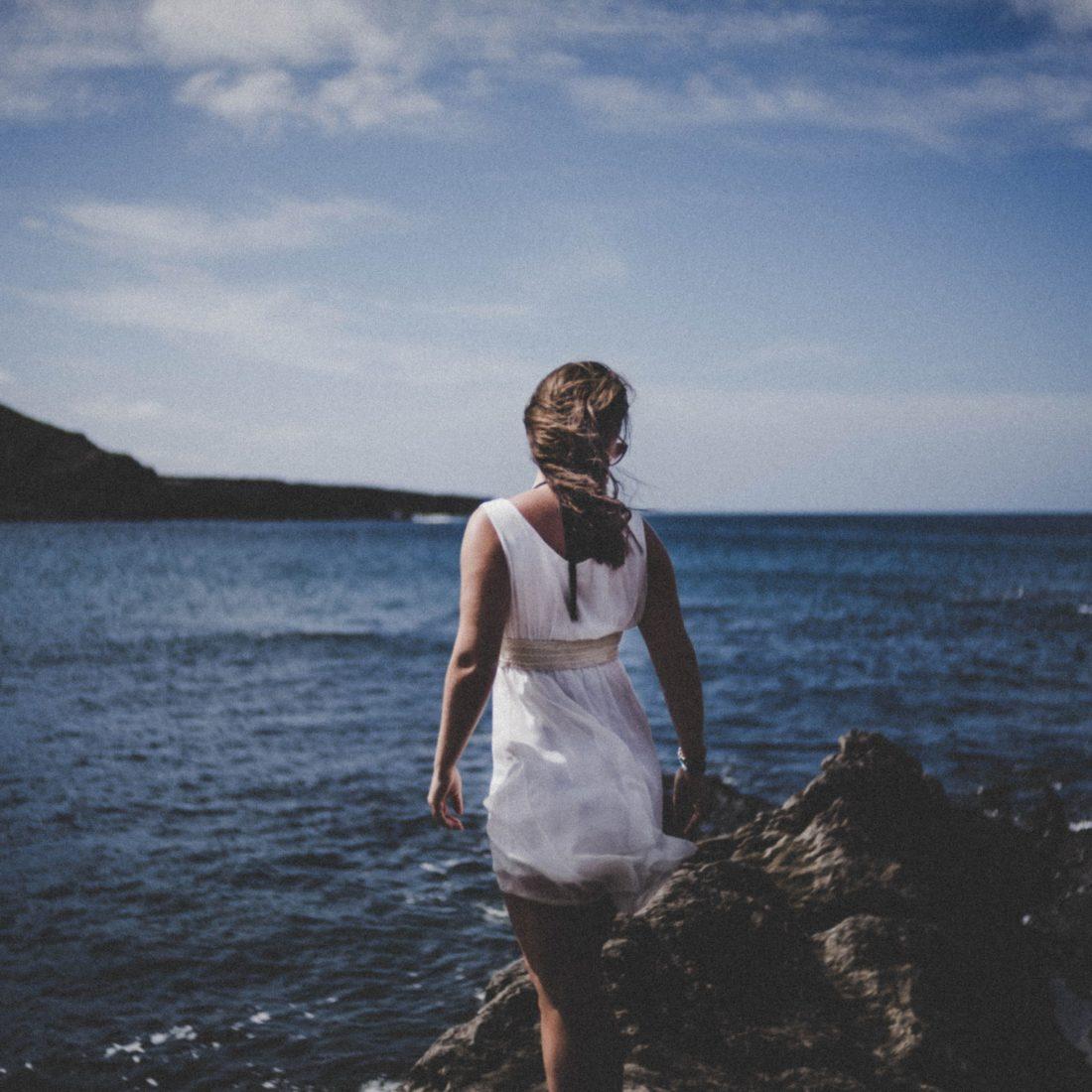 Mujer con vestido blanco mirando el mar